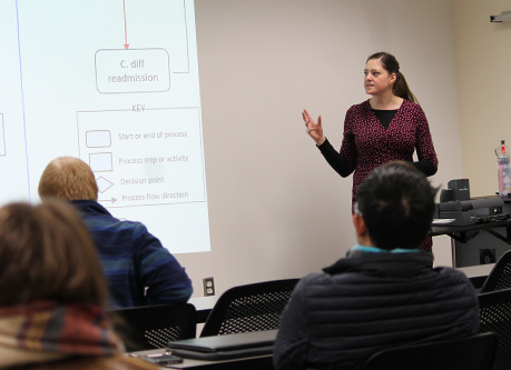 An instructor discusses different approaches to a study design with her class