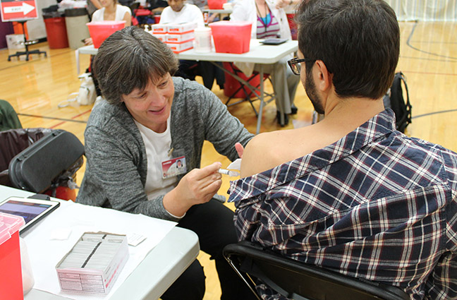 Professor Mary Hayney (Pharmacy Practice Division) provides a vaccination to a UW-Madison student.
